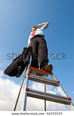Businessman, standing on a ladder, representing the manager with a helicopter overview of his business. - stock photo