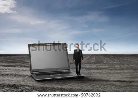 Businessman standing on a laptop on a field