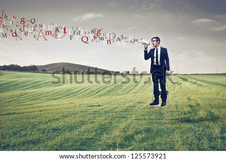 Businessman standing on a large field using a megaphone from which comes out colored words - stock photo