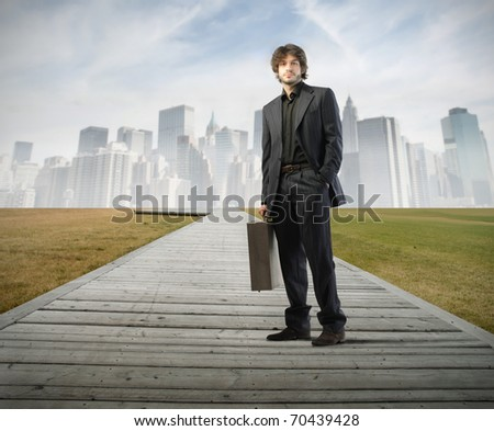 Businessman standing on a path with cityscape on the background - stock photo