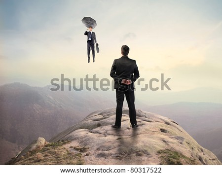Businessman standing on a peak and observing another businessman flying - stock photo