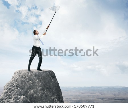 Businessman standing on a peak with butterfly net in his hands - stock photo