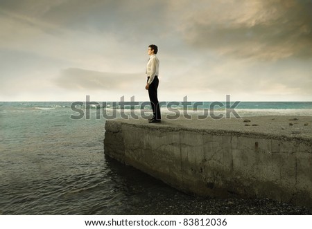 Businessman standing on a pier over the sea - stock photo