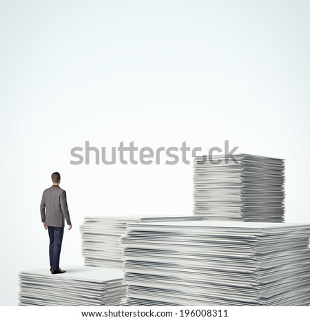 Businessman standing on a pile of blank documents - stock photo