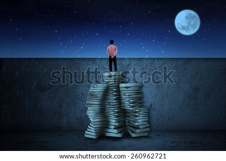Businessman standing on a pile of books and look the sky at night with moon and stars - stock photo