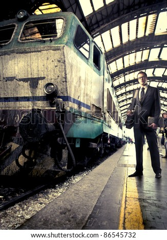 Businessman standing on a platform beside a train - stock photo