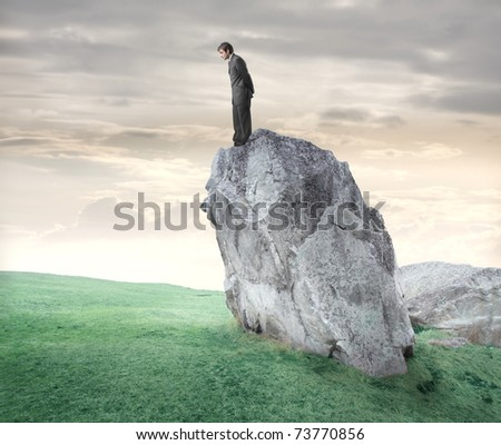 Businessman standing on a rock and looking downwards - stock photo