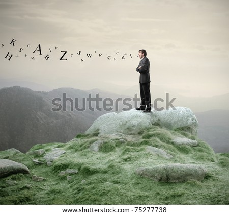 Businessman standing on a rock and shouting with alphabet letters coming out of his mouth - stock photo