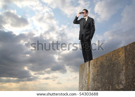 Businessman standing on a rock and using binoculars - stock photo