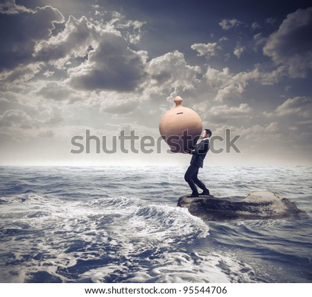 Businessman standing on a rock in the middle of a slight sea and holding a giant money box - stock photo
