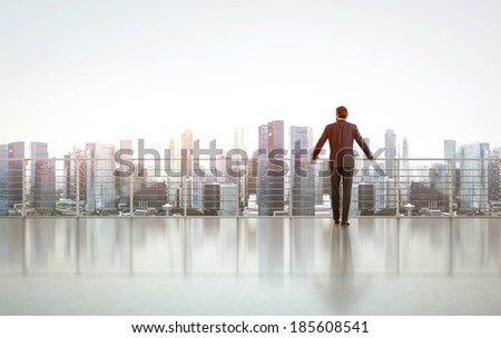 Businessman standing on a roof and looking at city  - stock photo