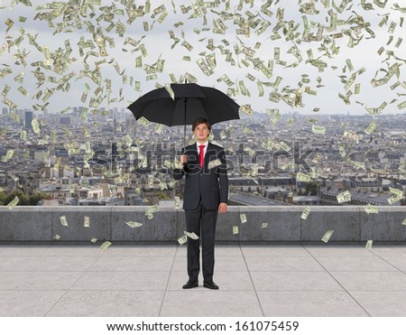 Businessman standing on a roof in the rain of money.1,5,10,20,50,100 dollar bills - stock photo