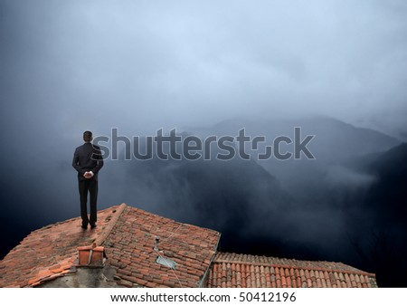 Businessman standing on a rooftop looking over a foggy landscape - stock photo