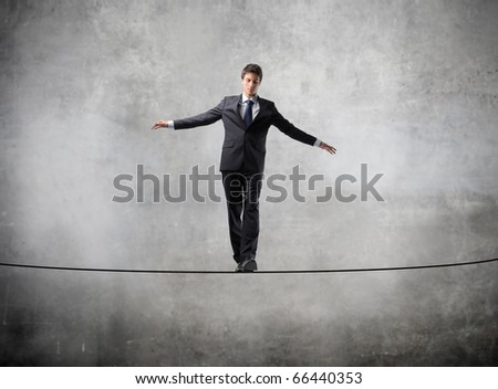 Businessman standing on a rope - stock photo