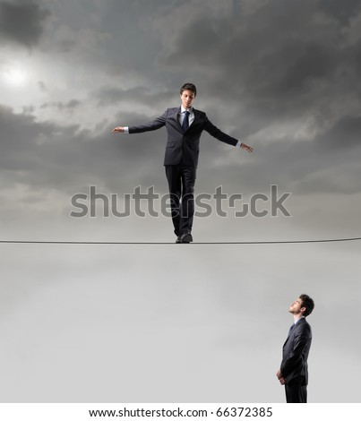 Businessman standing on a rope and other businessman looking at him - stock photo