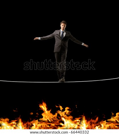Businessman standing on a rope over a fire - stock photo