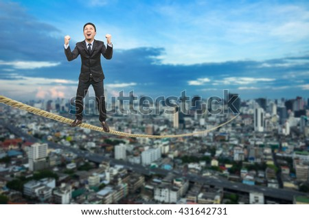 Businessman standing on a rope over blurred cityscape.