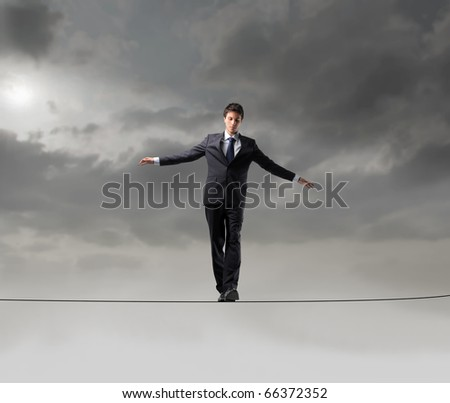 Businessman standing on a rope over the void - stock photo