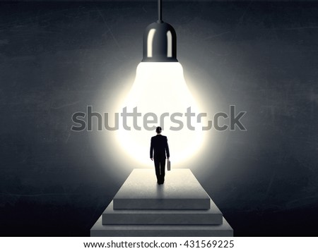 Businessman standing on a step in front of a huge light bulb, concept of having an idea. - stock photo