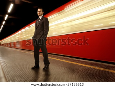 businessman standing on a subway platform - stock photo