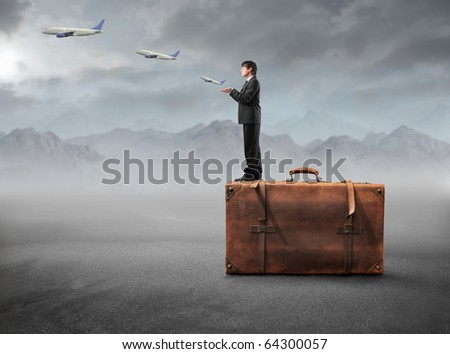 Businessman standing on a suitcase with airplanes flying from his hands - stock photo