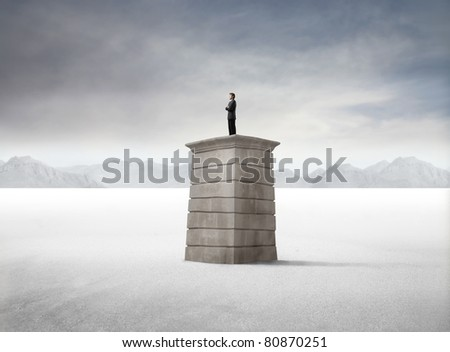 Businessman standing on a tower in the desert