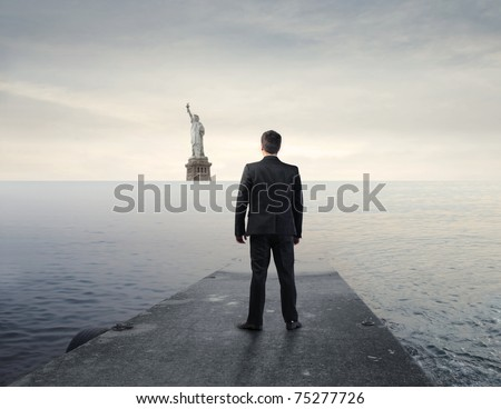Businessman standing on a wharf with Statue of Liberty in the background - stock photo