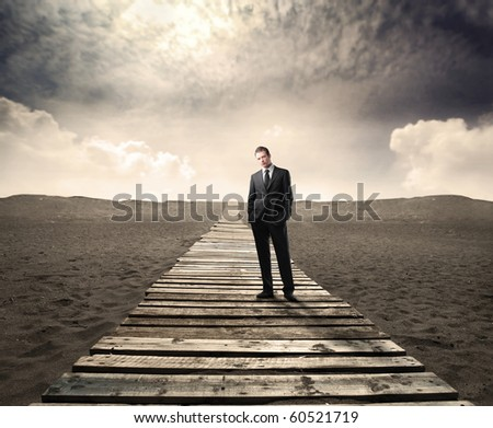 Businessman standing on a wooden path on a desert - stock photo