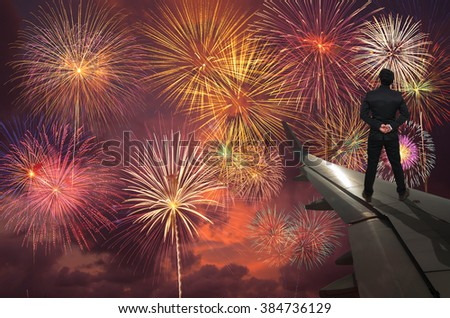 businessman standing on airplane wing which can see Fantastic festive colorful fireworks, Challenge and success business concept