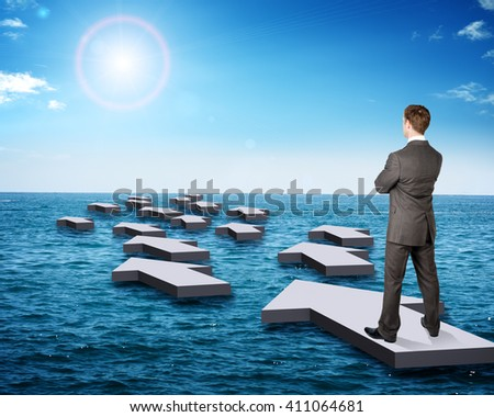 Businessman standing on arrow in sea with sun, side view