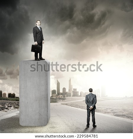 Businessman standing on bar and looking down at colleague - stock photo