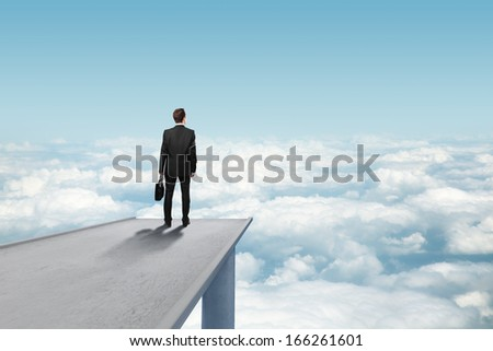 businessman standing on concrete bridge an looking clouds - stock photo