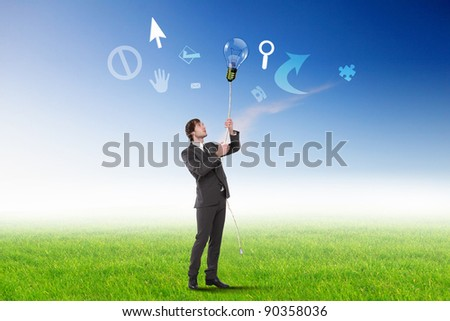 Businessman standing on green grass and thinking creatively - stock photo