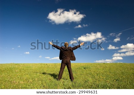 Businessman standing on green grass - arms outstretched, deep blou sky and white clouds - stock photo