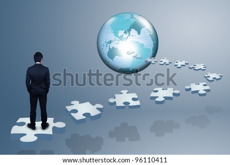 Businessman standing on jigsaw. - stock photo