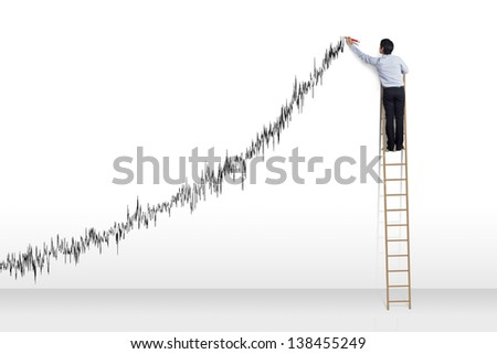 Businessman standing on ladder drawing diagrams and growth graph - stock photo