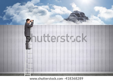 Businessman standing on ladder using binoculars against mountain peak through the clouds - stock photo