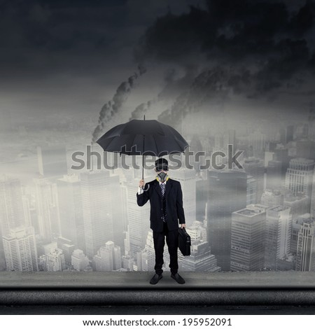 Businessman standing on rooftop wearing a gas mask while holding an umbrella and briefcase