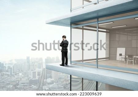 businessman standing on skyscraper and looking to city - stock photo