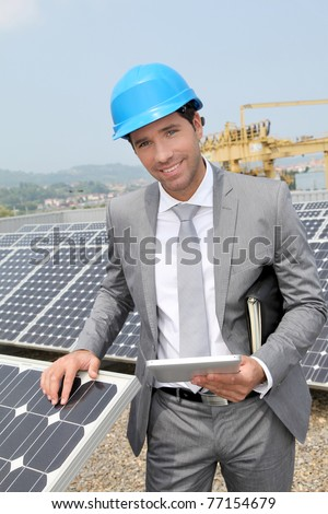 Businessman standing on solar panel installation - stock photo