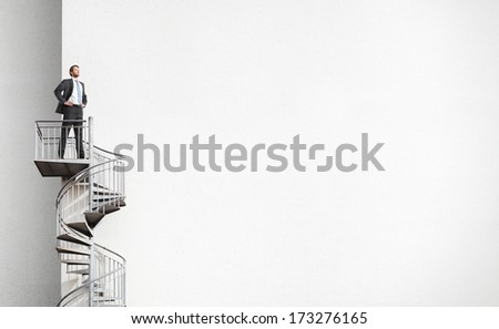 Businessman standing on spiral staircase - stock photo
