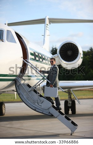 Businessman standing on stairs to private jet - stock photo