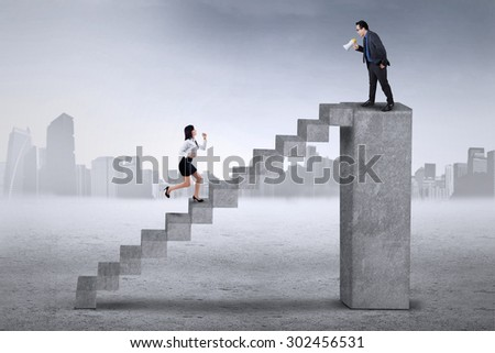 Businessman standing on the bar and calling his colleague to run faster on the stair - stock photo