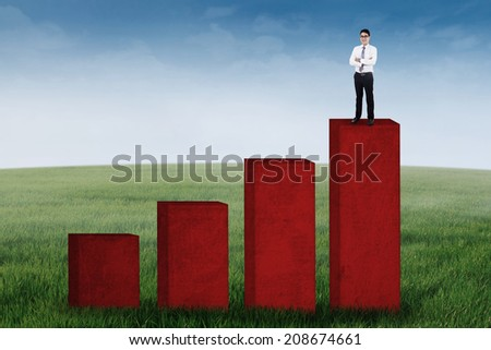 Businessman standing on the business chart, shot outdoors