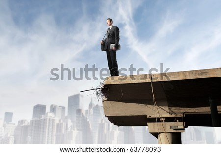 Businessman standing on the edge of a bridge