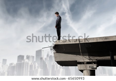 Businessman standing on the edge of a broken bridge and looking into the void - stock photo