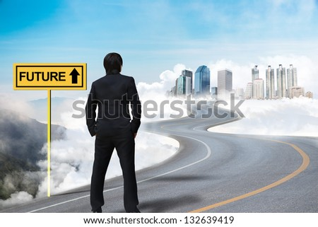Businessman standing on the empty road and watching the future city on the cloud