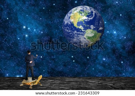 """Businessman standing on the Moon with Earth in the background """"Elements of this image furnished by NASA"""". - stock photo"""