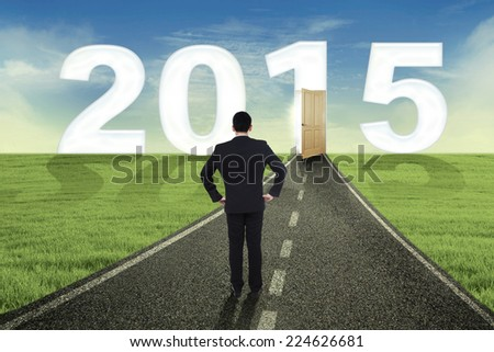 Businessman standing on the road and looking at the door to future 2015 - stock photo