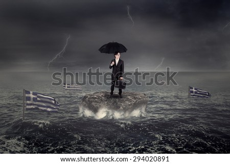 Businessman standing on the rock under umbrella with Greece flag sink on the sea. Concept of Greece economic crisis - stock photo